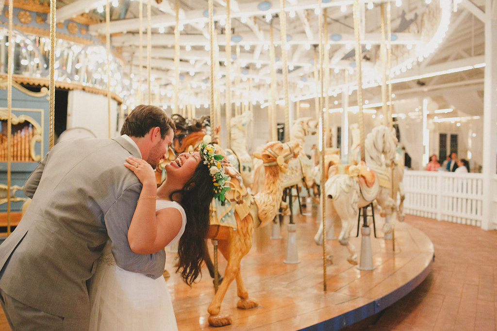 Bride and groom having fun on a merry-go-round.