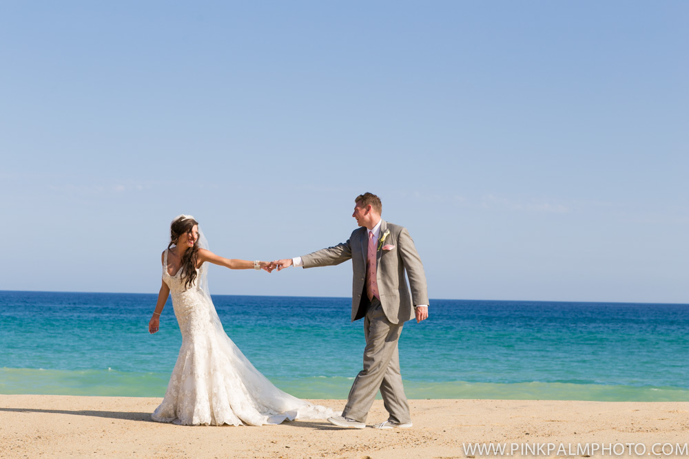 Bride and groom holding hands on the beach