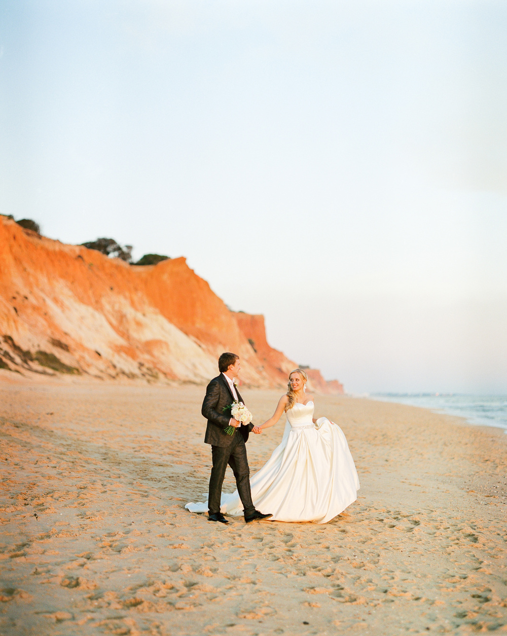Bride and groom walking on the beach on their wedding day